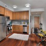 Серый коврик на коричневом полу кухни