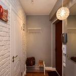 Светлая стена из кирпича в дизайне коридора