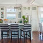 Функциональный белый гарнитур на кухне с двумя окнами