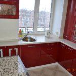 Кухня в многоэтажке в красном цвете и с мойкой у окна