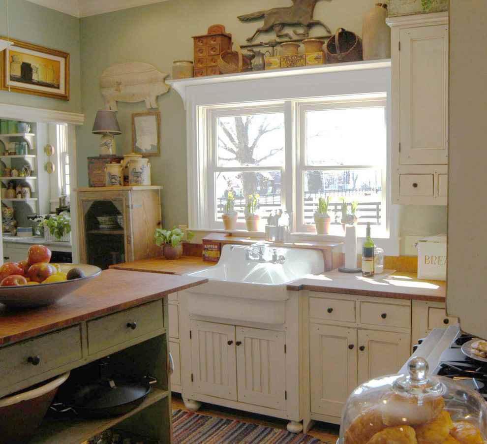Белая мойка под окном деревенской кухни
