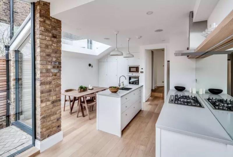 Интерьер белой кухни загородного дома с низким потолком